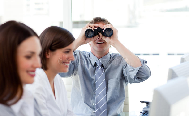 Charismatic manager looking through binoculars. In the office royalty free stock photography