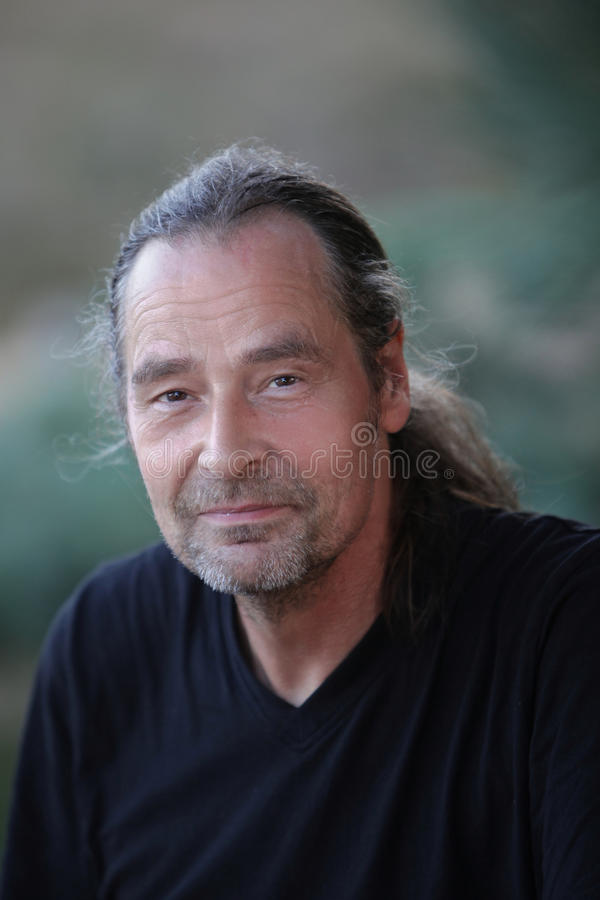 Charismatic middle-aged man with a ponytail royalty free stock image