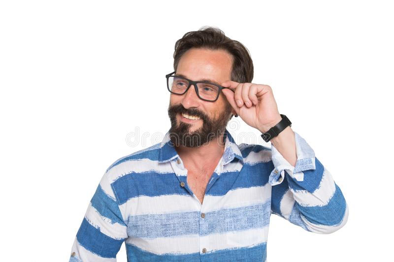 Charismatic positive bearded man looking away through glasses royalty free stock photography