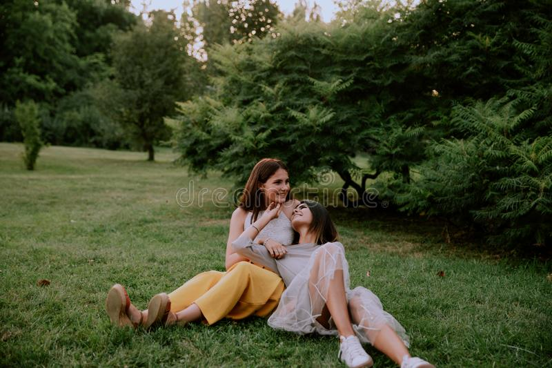 Charismatic and smiling large two pretty ladies falling down on the grass enjoying the time spending together in the stock photo