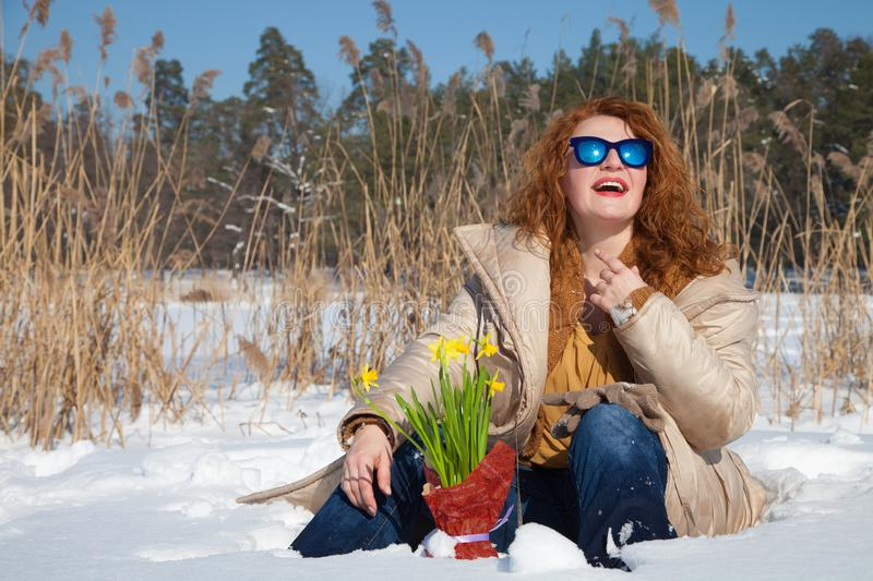Charismatic smiling woman looking up through sunglasses with rural nature on background. Wonderful weather. Smiling red haired woman sitting in snow while royalty free stock images