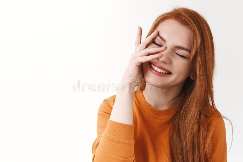 Charismatique jeune rougeâtre en pull orange, les yeux fermés et souriant joyeusement, touchant la peau pure photographie stock