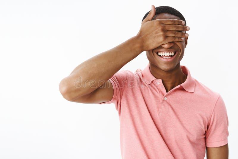 Charismatische grappige en gelukkige aantrekkelijke Afrikaanse Amerikaanse mensen sluitende ogen met palm niet om te gluren vreug stock foto's