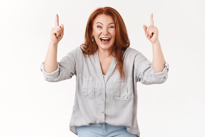 Charismatische, mooi uitziende, gelukkige roodkopige vrouw van middelbare leeftijd die lachte met vrolijk giggle die de handen om stock afbeelding