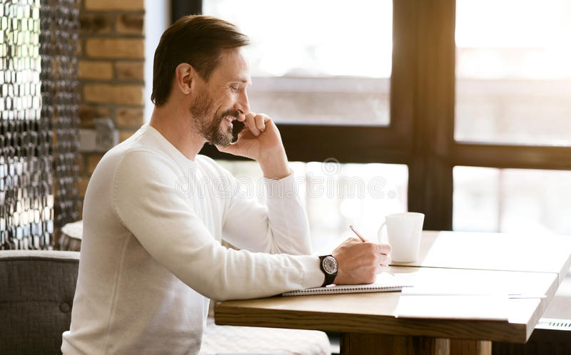 Charismatischer bärtiger Mann, der telefonisch im Café spricht lizenzfreie stockfotos