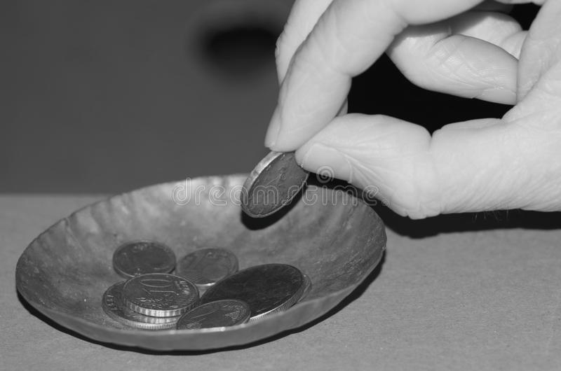 Charity or Begging. A man's hand gives alms in a tiny plate for charity stock photos