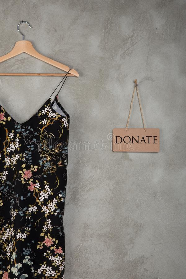 Charity concept - blackboard with text Donate and beautiful dress in floral pattern on a hanger stock photo