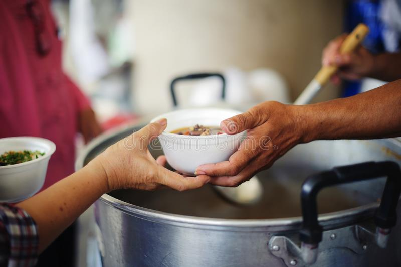Charity food is the hope of the poor who have no money: concept of begging food : Volunteers Share Food to the Poor to Relieve. Hunger stock images