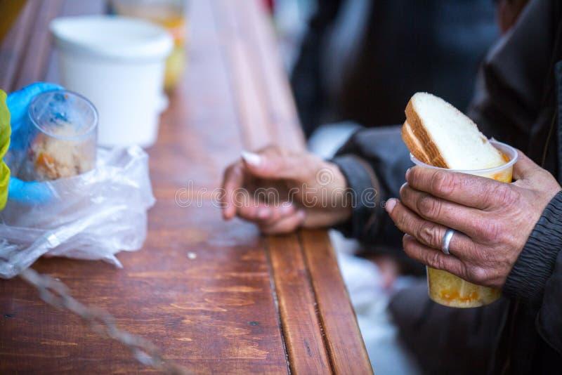 charity A luta contra a pobreza Os voluntários distribuíram refeições quentes aos povos na necessidade Dia de inverno frio imagem de stock royalty free