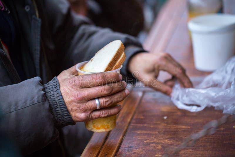 charity A luta contra a pobreza Os voluntários distribuíram refeições quentes aos povos na necessidade Dia de inverno frio na cid fotos de stock royalty free