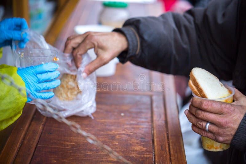 charity A luta contra a pobreza Os voluntários distribuíram refeições quentes aos povos na necessidade Dia de inverno frio na cid foto de stock