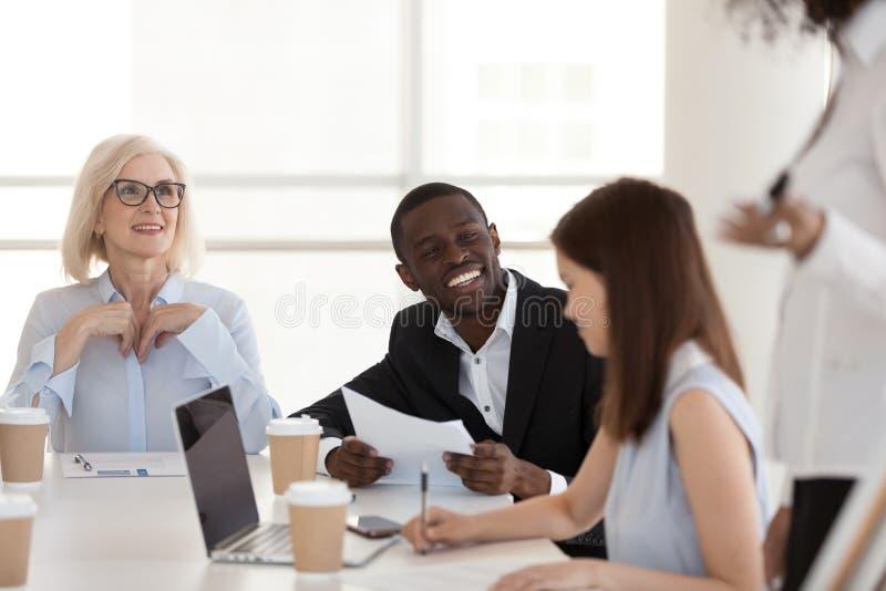 Charla afroamericana emocionada del empleado con los colegas en el informe imagen de archivo