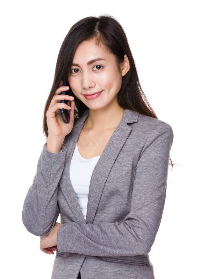 Charla asiática de la empresaria al teléfono móvil foto de archivo libre de regalías
