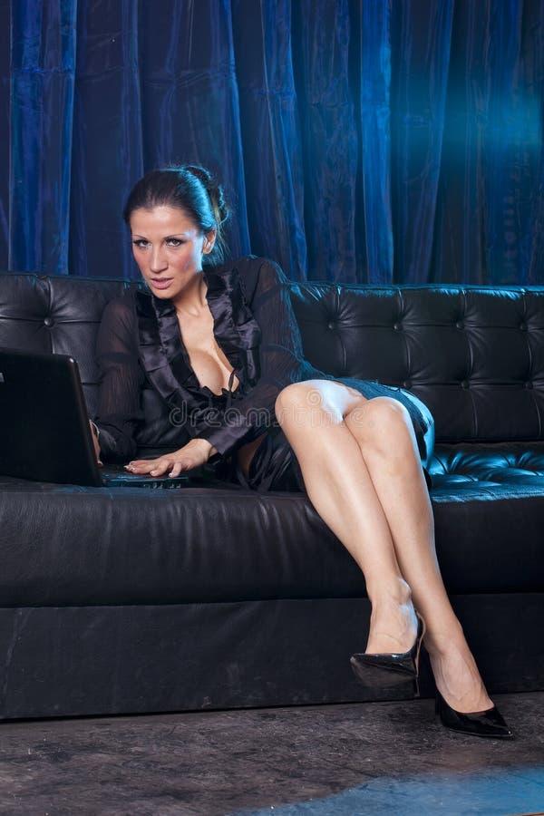 Charla atractiva - mujer atractiva que usa el ordenador portátil fotos de archivo