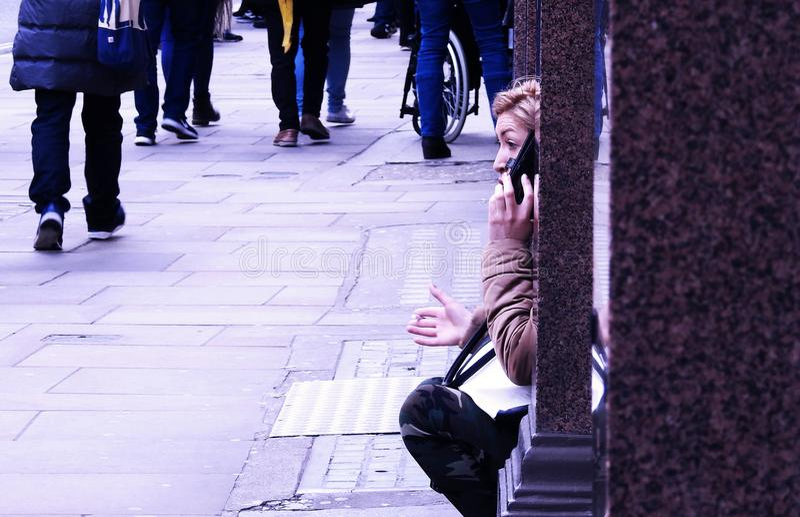 Charla de la calle Una mujer se sienta en una alcoba de una ventana de la tienda que tiene una discusión heated en su teléfono el fotografía de archivo libre de regalías