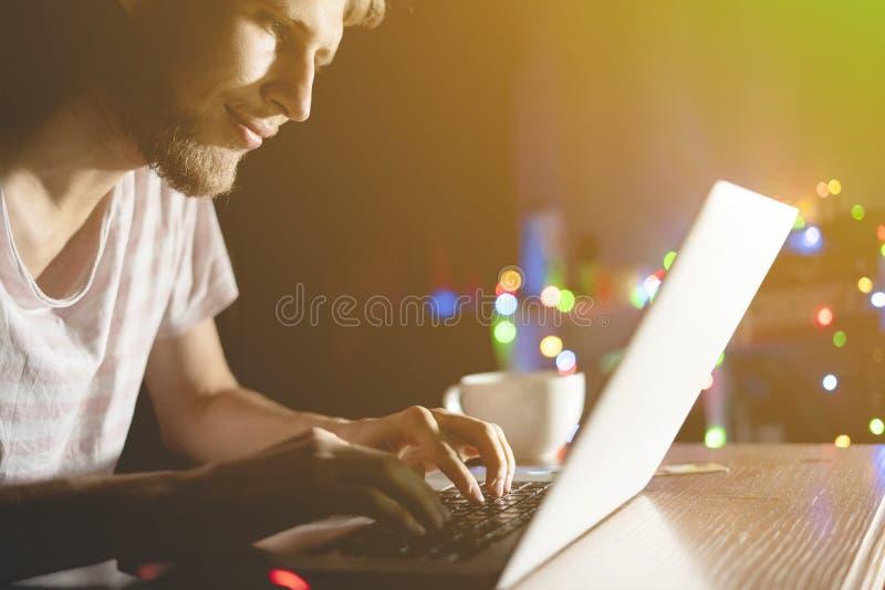 Charla del hombre joven en red social con los amigos que usan el teléfono y el ordenador portátil tarde en la noche d foto de archivo