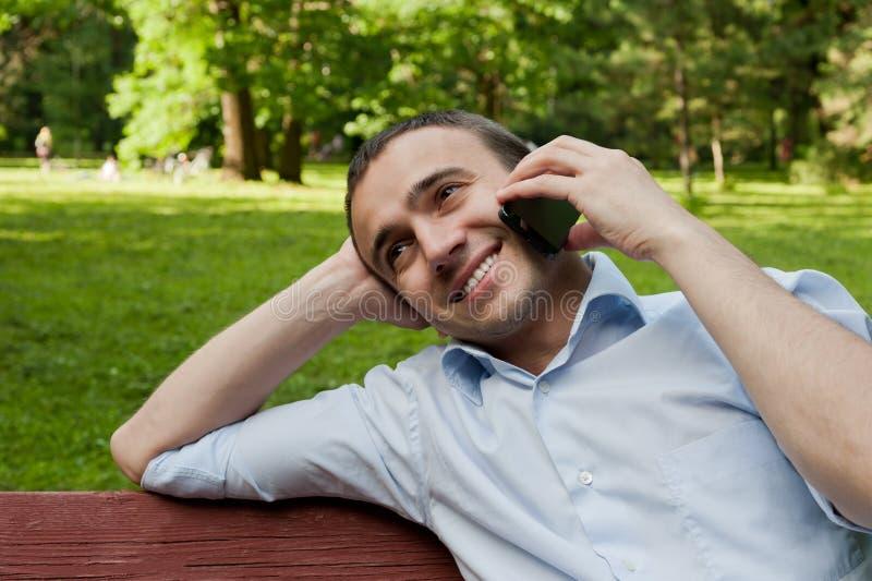 Charla del hombre por el teléfono en el parque fotografía de archivo
