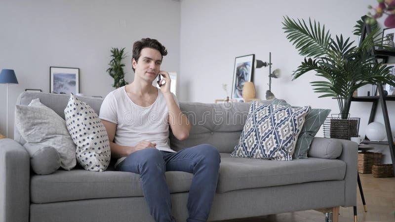 Charla del teléfono, hombre adulto que asiste a llamada en el trabajo imagen de archivo