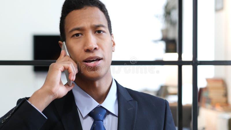 Charla del teléfono, hombre de negocios negro Attending Call en el trabajo foto de archivo