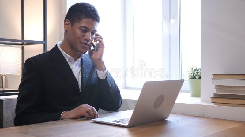 Charla del teléfono, hombre de negocios negro Attending Call en el trabajo fotografía de archivo