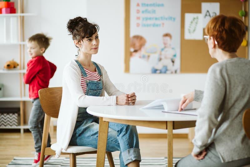 Charla del terapeuta del niño de ADHD con la madre y hacer preguntas durante la primera sesión fotografía de archivo