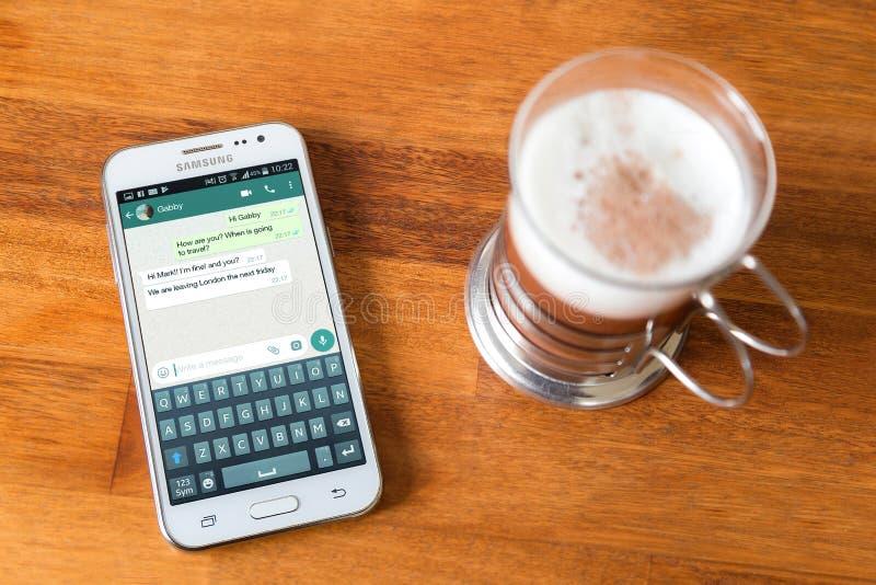 Charla del uso del whatsapp en la pantalla del teléfono celular imágenes de archivo libres de regalías