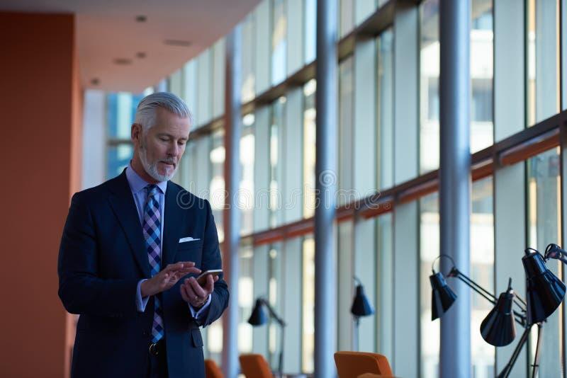 Charla mayor del hombre de negocios sobre el teléfono móvil imágenes de archivo libres de regalías