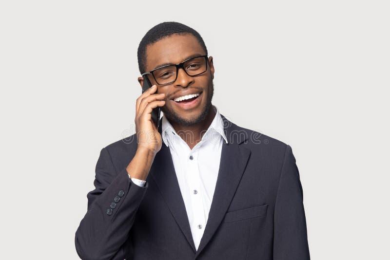 Charla negra sonriente del hombre de negocios sobre el teléfono móvil aislado en estudio fotografía de archivo libre de regalías