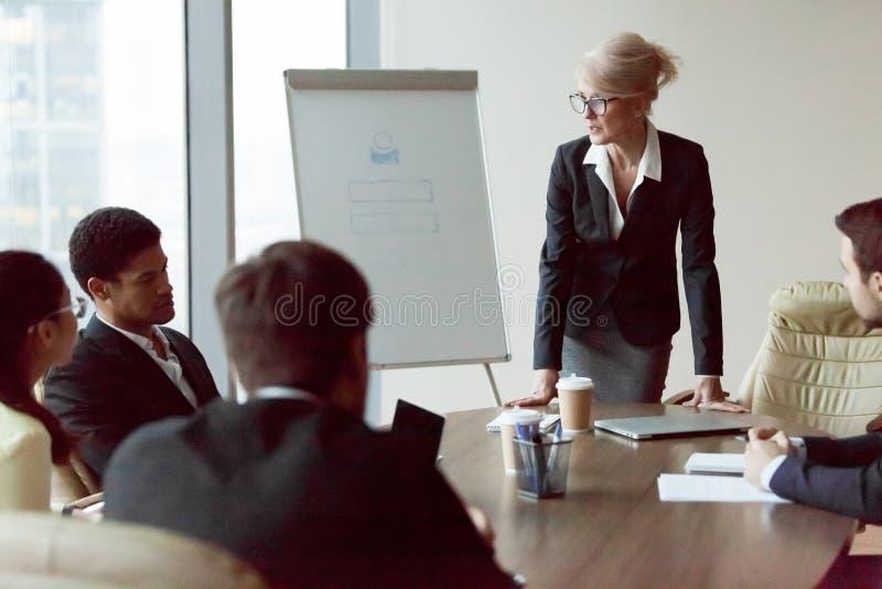 Charla seria de la empresaria durante el informe de la compañía en oficina fotos de archivo