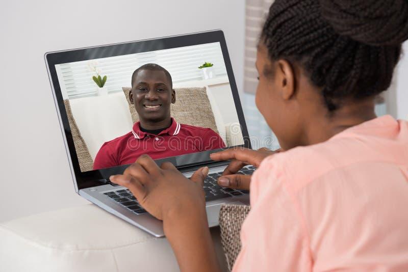 Charla video de la mujer con el hombre en el ordenador portátil fotos de archivo libres de regalías