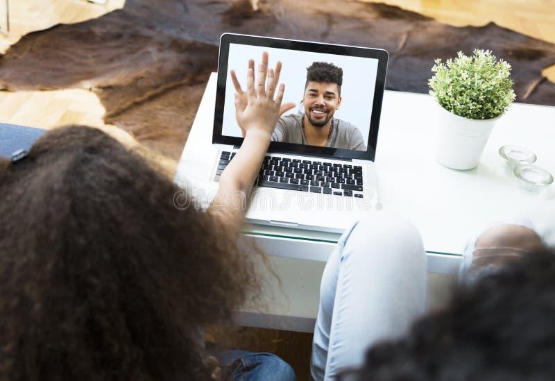 Charla video del niño sobre un ordenador portátil con su padre fotografía de archivo