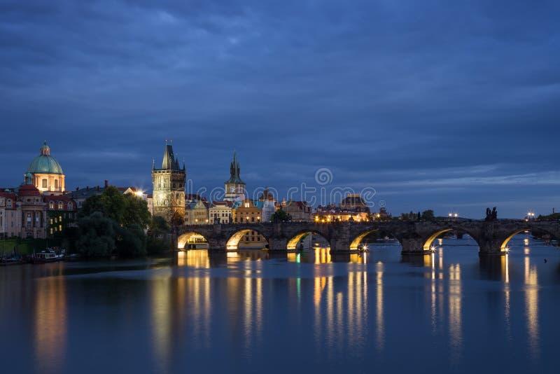 Charles Bridge e vecchie costruzioni a Praga alla notte fotografia stock