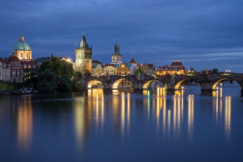 Charles Bridge e vecchie costruzioni a Praga alla notte fotografie stock libere da diritti