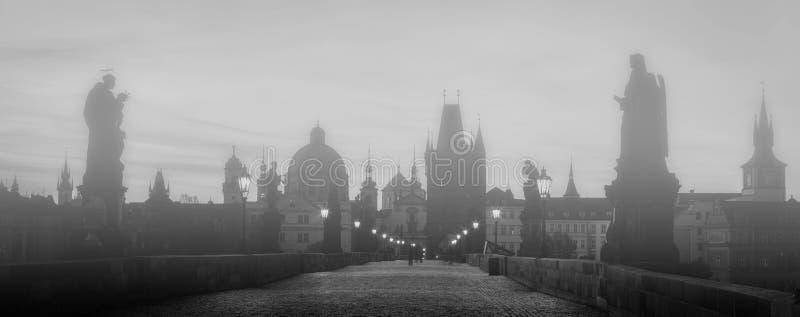 Charles Bridge en la niebla en la salida del sol, Praga, República Checa Estatuas dramáticas y torres medievales imagen de archivo