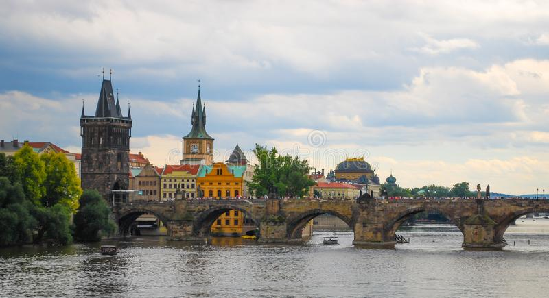 Charles Bridge i staden av Prague Karlův mest på en mulen sommardag med turister som korsar bron för stad för Vlatva river/den g royaltyfri bild