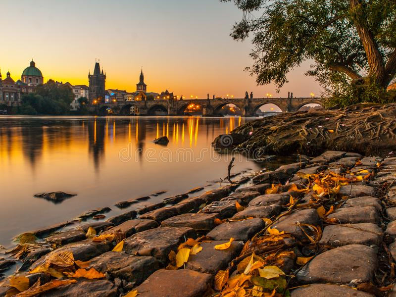 Charles Bridge with Old Town Bridge Tower reflected in Vltava River at morning sunrise time, Prague, Czech Republic.  stock photos