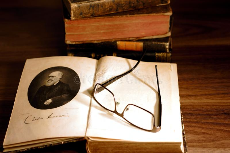 Charles Darwin`s `The origin of species` in front of a pile of 19th century books. royalty free stock photography
