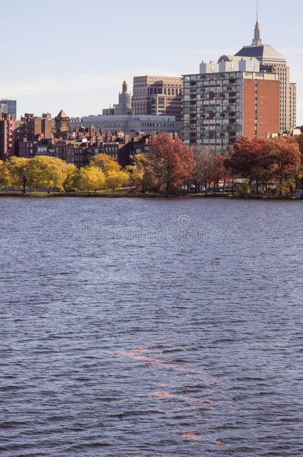 Charles River with fall foilage. Charles river in boston with the classical fall colors and showing the city architecture. Leaves on the water point to the city royalty free stock photography