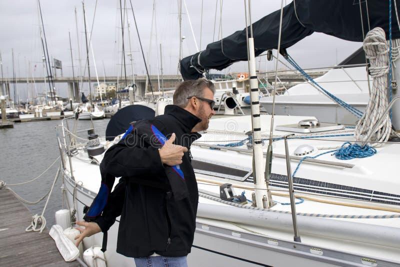 Charleston Marina South Carolina, 17 Februari, 2018 - mens die op reddingsvest naast zeilboot bij de jachthaven van Charleston wo stock afbeelding