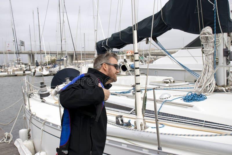 Charleston Marina South Carolina, 17 Februari, 2018 - mens die op reddingsvest naast zeilboot bij de jachthaven van Charleston ze royalty-vrije stock afbeeldingen
