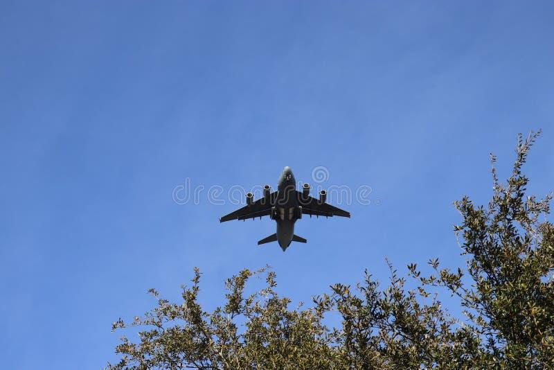 Charleston South Carolina January 23 2018 aviões de carga da força aérea do C17 de Boeing que voam baixo à terra e sobre a árvore imagens de stock royalty free