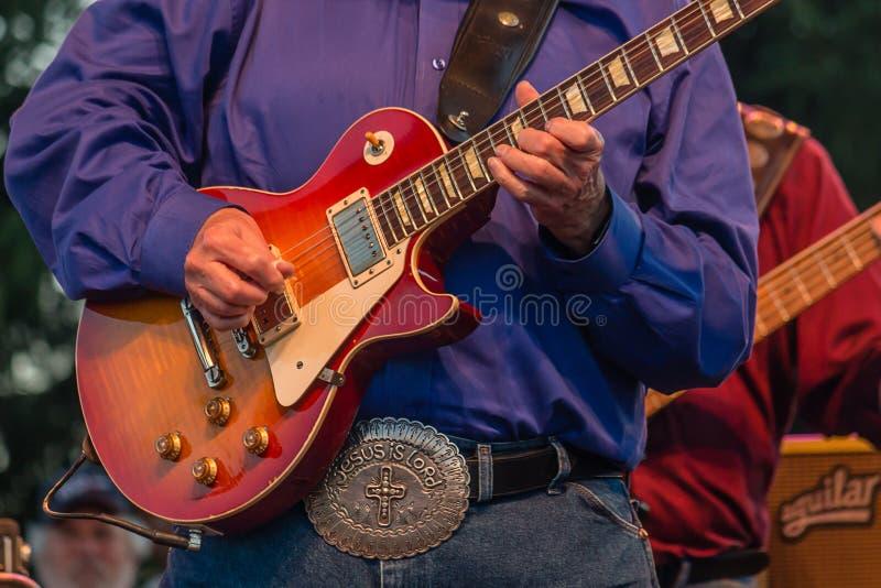 Charlie Daniels Guitar och Jesus Is Love Belt Buckle royaltyfri foto
