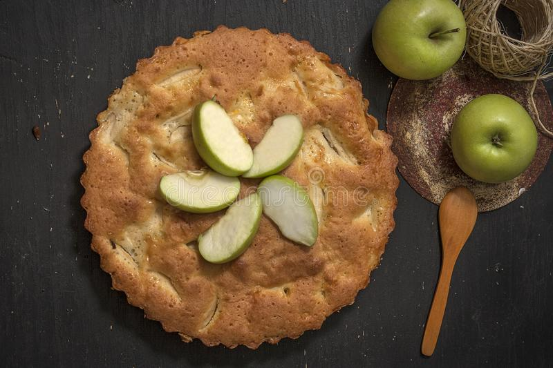 Charlotte apple pie on a black wooden table with slices of green apples. Top view royalty free stock image