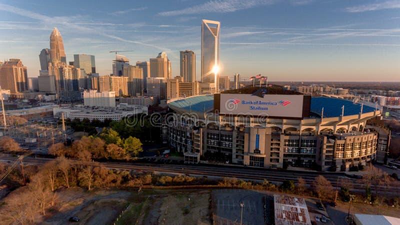 Charlotte, NC-Skyline nahe Sonnenuntergang mit Bank of Amerika-Stadion in der Front lizenzfreie stockfotografie