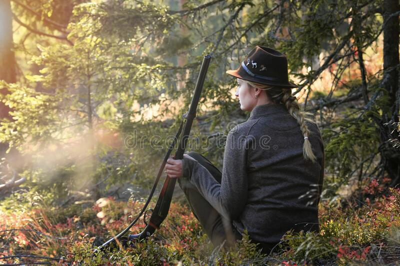 Charm of the setting sun in the mountains. Young beautiful woman on hunting with a gun. Forest, moutains, outdor, hunter woman stock photo