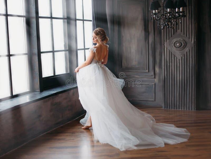 Charma ängel i snövit klänningdans i slotttorn med stora fönster, en ny berättelse om Cinderella och snö royaltyfria foton