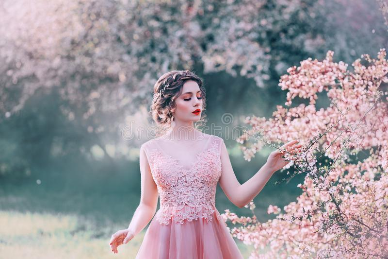 Charma damen, i att blomma tr?dg?rden, sl?r flickan med samlat h?r f?rsiktigt filialer av tr?d med blommor, porslindocka arkivfoton