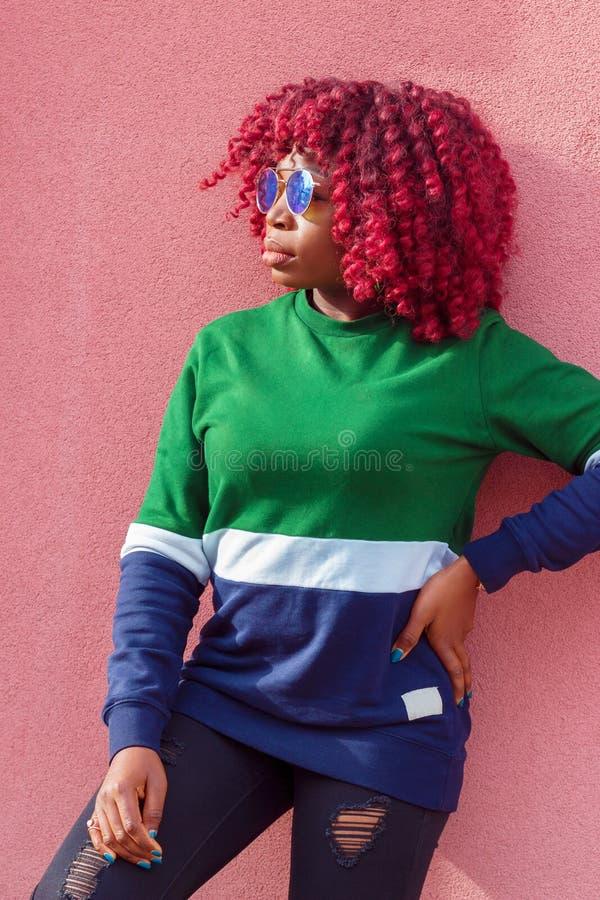 Charma den afrikanska kvinnan med blå solglasögon Trendig och stilfull flicka som poserar nära den rosa väggen arkivfoton