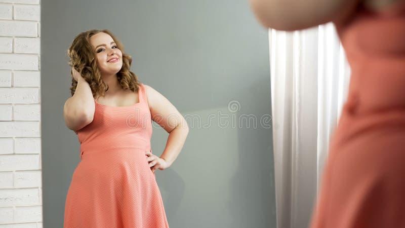 Charma den fylliga damen som ser, i spegel och att beundra sig, kropprealitet royaltyfri bild