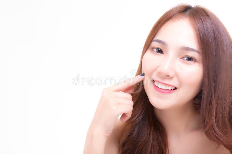 Charma den härliga för bruksfinger för ung kvinna kinden för press och att visa framsidahud som är slät och som är mjuk med leend royaltyfri bild